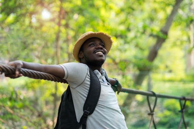 Viaggiatore africano dell'uomo con lo zaino che sorride con il fondo verde della natura.