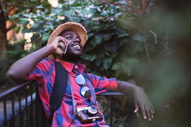 Viaggiatore africano dell'uomo in occhiali da sole e camicia facendo uso di uno smartphone.