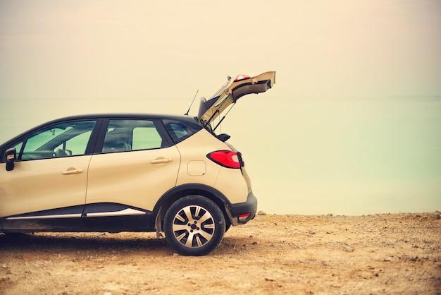 Viaggiatore alla moda felice della giovane donna sulla strada della spiaggia che si siede sull'automobile bianca dell'incrocio