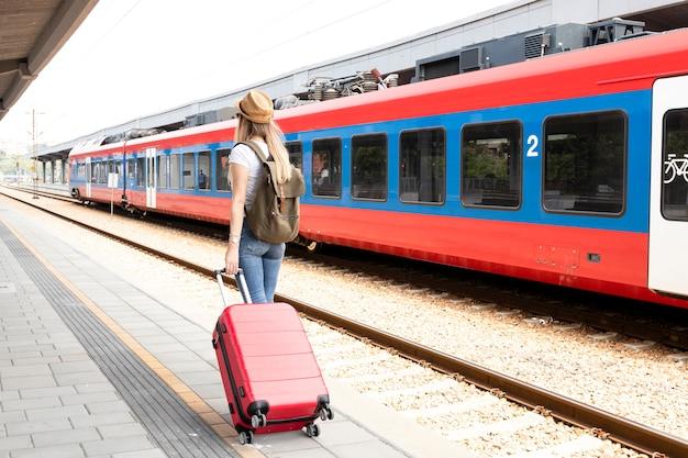 Viaggiatore alla stazione ferroviaria da dietro