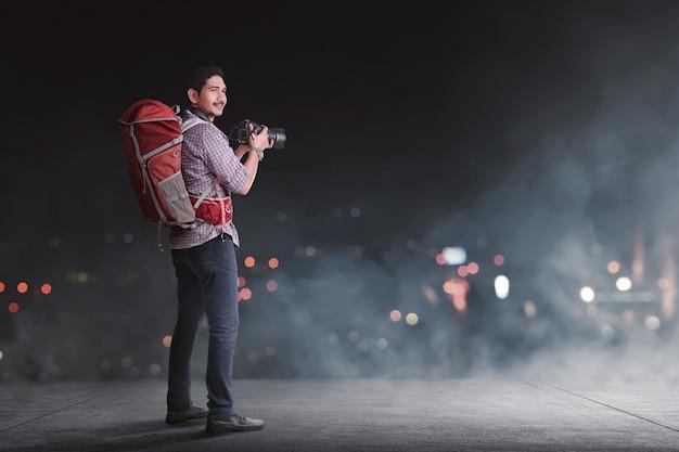 Viaggiatore asiatico bello con lo zaino e la macchina fotografica