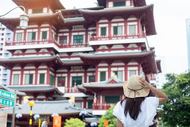 Viaggiatore asiatico che guarda al tempio della reliquia del dente di buddha in chinatown singapore