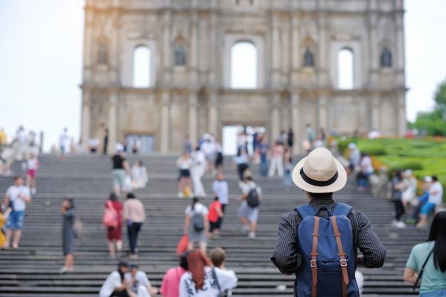 Viaggiatore asiatico dei pantaloni a vita bassa che guarda alle rovine di st paul, macao