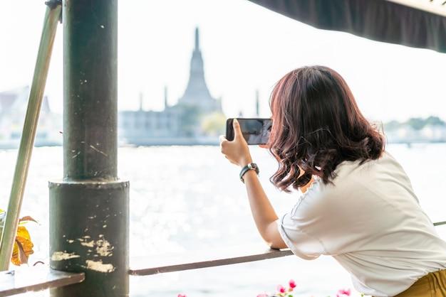 Viaggiatore asiatico della donna che prende una foto in caffè