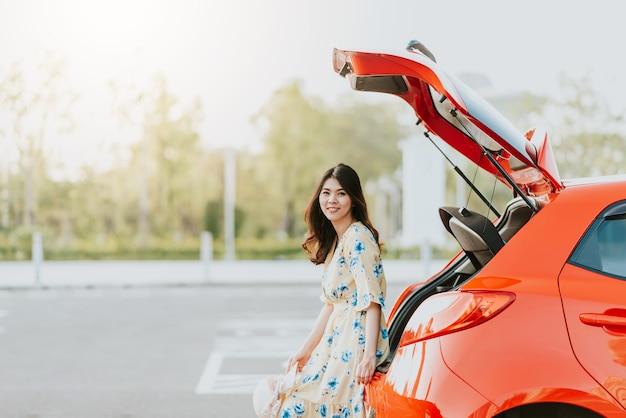 Viaggiatore asiatico della donna che si siede sul tronco di automobile
