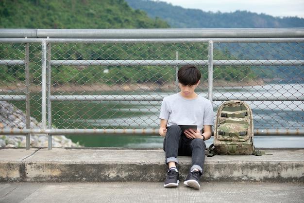 Viaggiatore asiatico seduto e utilizzando la tavoletta sul ponte sul fiume, con uno zaino posto sul lato. - immagine