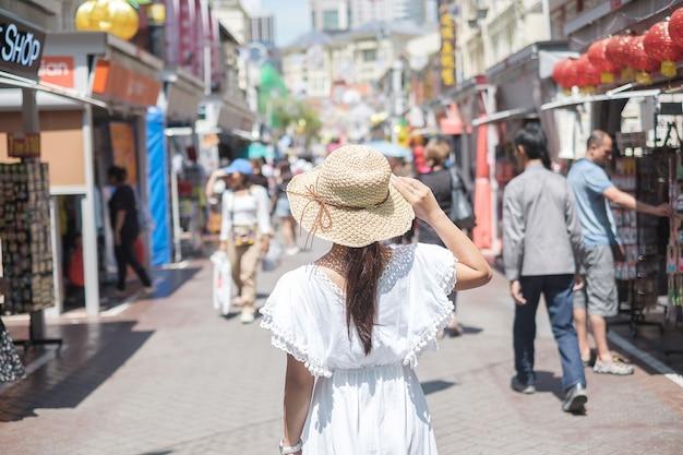 Viaggiatore che cammina al mercato di strada di chinatown a singapore.