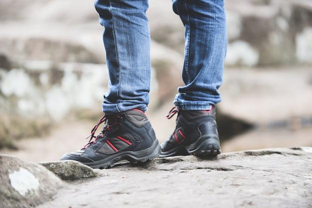 Viaggiatore che cammina nella foresta tra le montagne di roccia man escursionista gambe e piedi nei panni