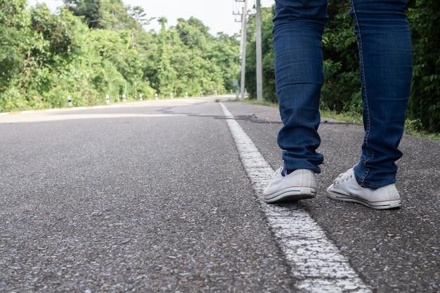 Viaggiatore che cammina sulla strada al parco naturale.