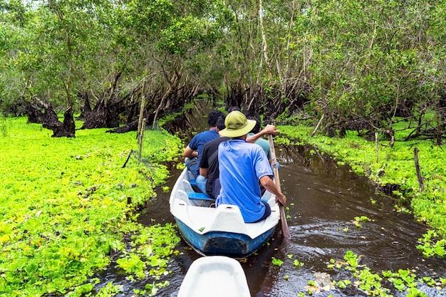 Viaggiatore che fa un giro turistico sopra la barca tradizionale nella foresta di tra su, viaggio di delta del mekong, vietnam