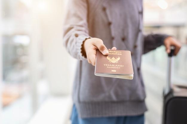 Viaggiatore che mostra il suo passaporto all'aeroporto