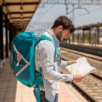 Viaggiatore con bersaglio medio guardando su una mappa