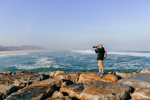 Viaggiatore con la macchina fotografica che prende foto di paesaggio oltre il mare
