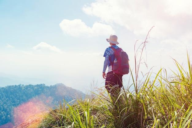 Viaggiatore con lo zaino in piedi e guardando avanti sulla cima della montagna con la luce del sole