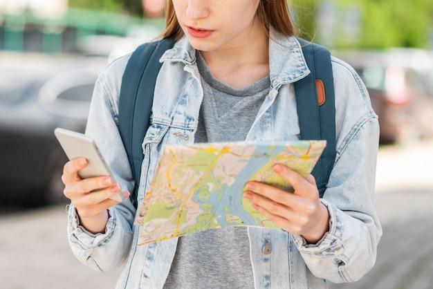 Viaggiatore con mappa e telefono cellulare