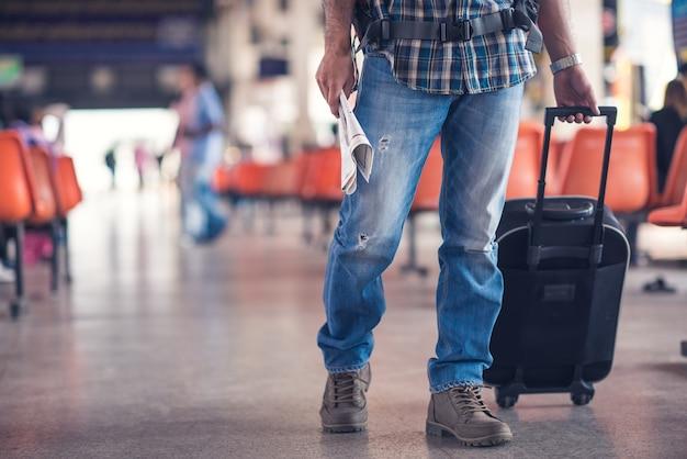 Viaggiatore con una valigia sulla stazione degli autobus