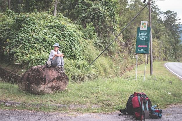 Viaggiatore con zaino e sacco a pelo che aspetta autostop sulla strada per il parco nazionale di kubah, sarawak, borneo, malesia.