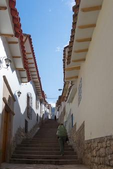 Viaggiatore con zaino e sacco a pelo che cammina in salita sulla scala a cusco, perù