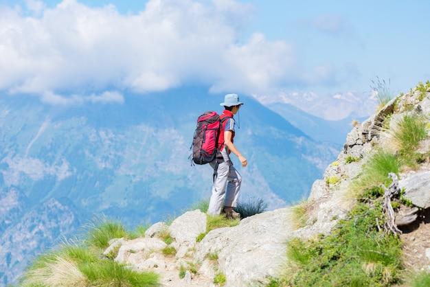 Viaggiatore con zaino e sacco a pelo che cammina sul sentiero in montagna. avventure estive sulle alpi.