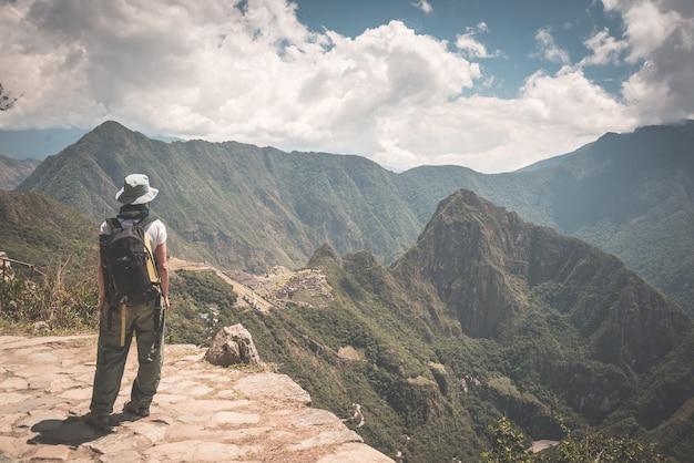 Viaggiatore con zaino e sacco a pelo che cammina sul sentiero inca sopra machu picchu, la destinazione di viaggio più visitata in perù