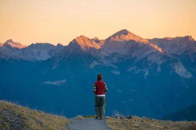 Viaggiatore con zaino e sacco a pelo che cammina sul sentiero nella montagna. avventure estive sulle alpi