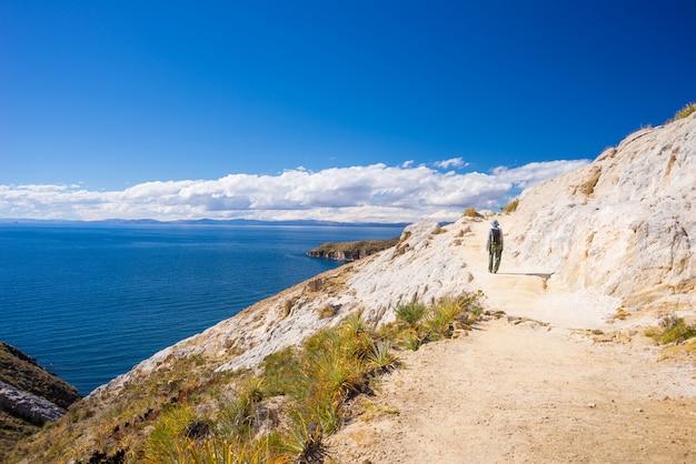 Viaggiatore con zaino e sacco a pelo che esplora i maestosi inca trails sull'isola del sole, il lago titicaca, tra le destinazioni di viaggio più panoramiche in bolivia. avventure di viaggio e vacanze nelle americhe.