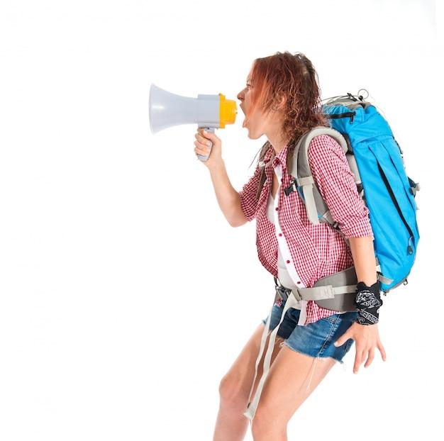 Viaggiatore con zaino e sacco a pelo che grida dal megafono sopra fondo bianco