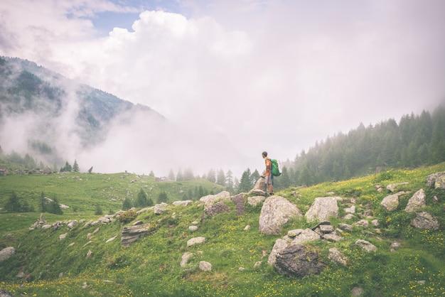 Viaggiatore con zaino e sacco a pelo che sta sul sentiero per pedoni della montagna, tonificato