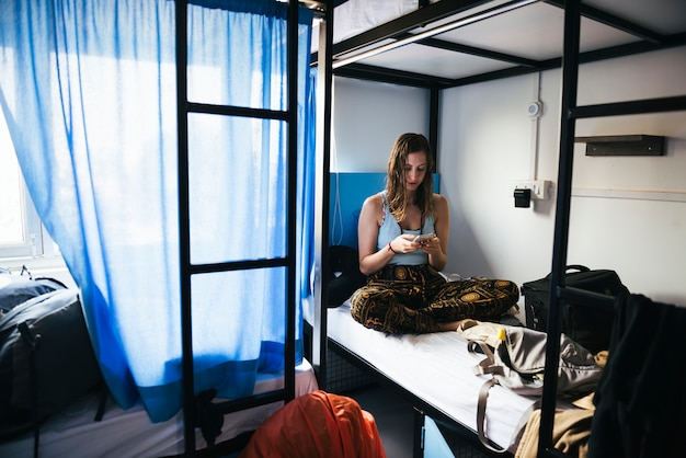 Viaggiatore con zaino e sacco a pelo che utilizza il suo telefono in un ostello a varanasi, india