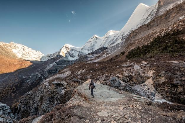 Viaggiatore con zaino e sacco a pelo dell'uomo che cammina alla scogliera con catena montuosa della neve