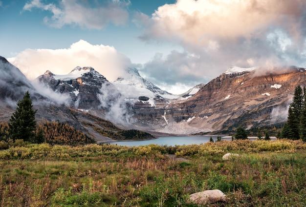 Viaggiatore con zaino e sacco a pelo dell'uomo che cammina sul campo nel parco provinciale di assiniboine di mattina