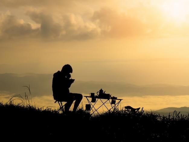 Viaggiatore con zaino e sacco a pelo dell'uomo della siluetta che mangia prima colazione sulla montagna all'alba.