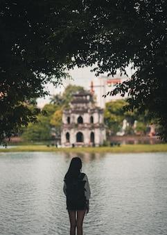 Viaggiatore con zaino e sacco a pelo della donna che esplora hanoi vietnam davanti al lago ed al monumento
