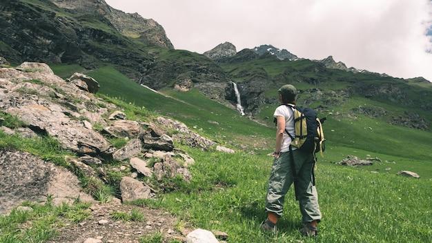 Viaggiatore con zaino e sacco a pelo della donna che fa un'escursione nel paesaggio idilliaco, nella cascata e nel prato di fioritura.