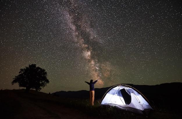 Viaggiatore con zaino e sacco a pelo della donna che ha un resto alla notte che si accampa in montagne. femmina in piedi accanto alla tenda illuminata con le mani sollevate, godendo della vista del meraviglioso cielo notturno pieno di stelle e via lattea