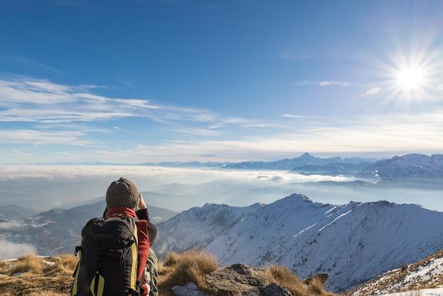 Viaggiatore con zaino e sacco a pelo della donna che riposa sulla cima della montagna.