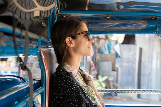 Viaggiatore con zaino e sacco a pelo della donna che viaggia nel trasporto pubblico in tailandia. songthaew è un modo economico per viaggiare tra i paesi asiatici. esperienza turistica il vero sud-est in asia. vacanze e concetto di viaggio.
