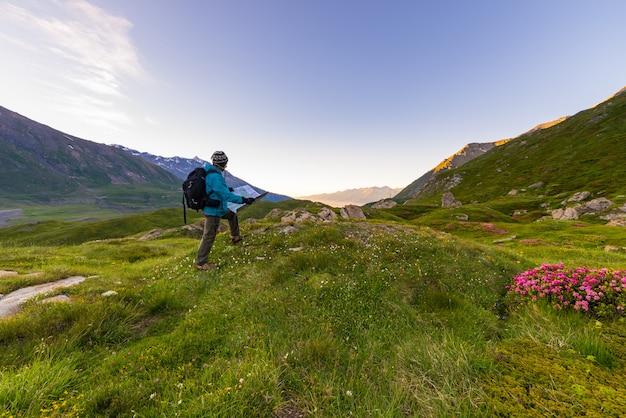 Viaggiatore con zaino e sacco a pelo della viandante con la mappa di trekking ad alba nelle alpi francesi italiane.
