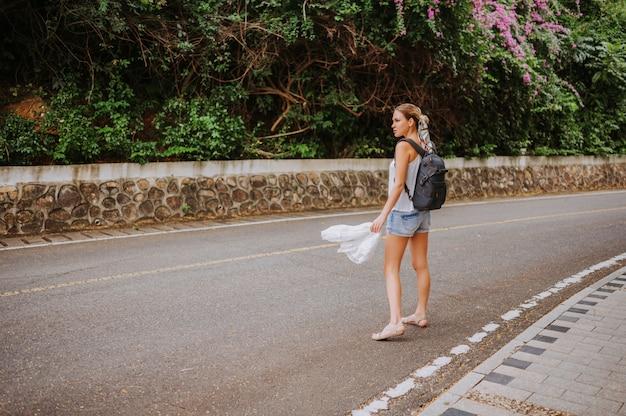 Viaggiatore con zaino e sacco a pelo donna bionda che cammina sul sentiero nella foresta tropicale, viaggi avventura natura in cina, bella destinazione turistica asia, viaggio di vacanze estive, copia spazio per banner