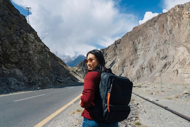 Viaggiatore con zaino e sacco a pelo femminile che cammina su un'autostrada montuosa