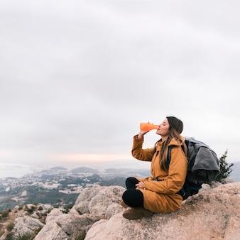 Viaggiatore con zaino e sacco a pelo femminile che si siede sulla cima della montagna che beve l'acqua