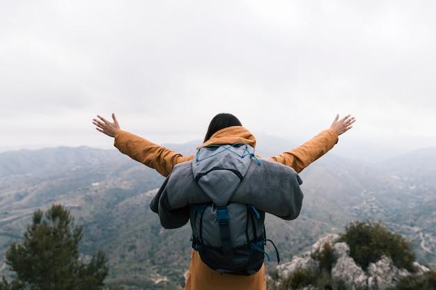 Viaggiatore con zaino e sacco a pelo femminile che sta sulla cima della montagna che ama la natura