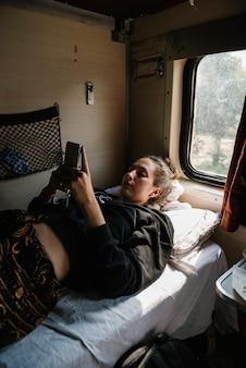 Viaggiatore con zaino e sacco a pelo femminile occidentale che utilizza il suo telefono nel treno indiano