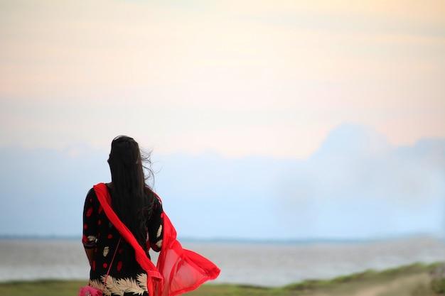 Viaggiatore con zaino e sacco a pelo incoraggiante della giovane donna al picco di montagna della spiaggia di alba