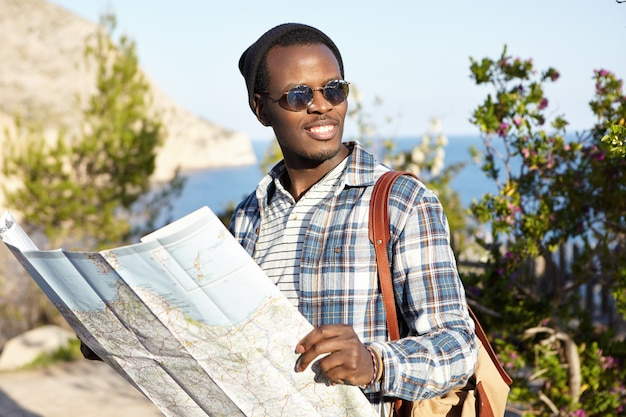 Viaggiatore con zaino e sacco a pelo maschio nero alla moda bello con la guida di viaggio di carta in sue mani che cercano il ristorante vegetariano mentre esplorando città europea durante il viaggio