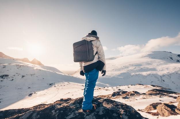 Viaggiatore con zaino e sacco a pelo posteriore che sta sulla roccia in valle nevosa