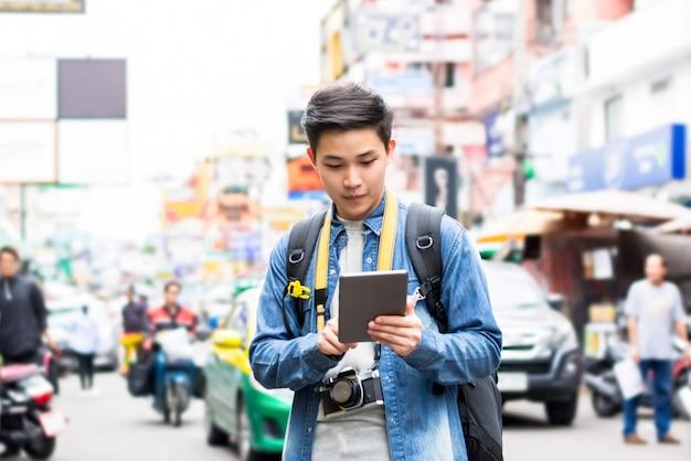 Viaggiatore con zaino e sacco a pelo turistico asiatico che utilizza compressa mentre viaggiando in strada tailandia di khao san