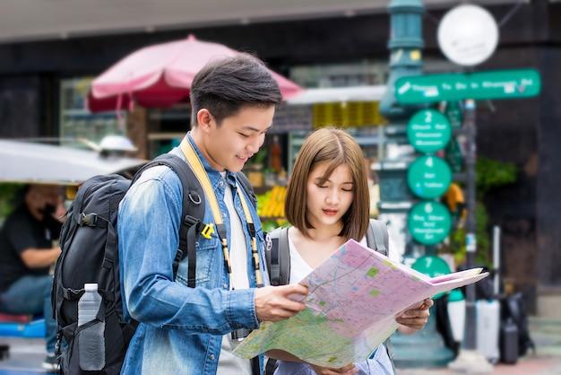 Viaggiatore con zaino e sacco a pelo turistico asiatico delle giovani coppie che cercano la direzione alla mappa