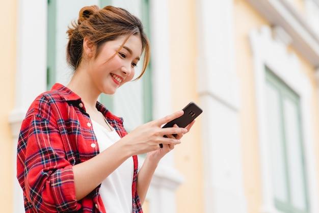 Viaggiatore con zaino e sacco a pelo turistico della donna asiatica che sorride e che usando smartphone che viaggia da solo