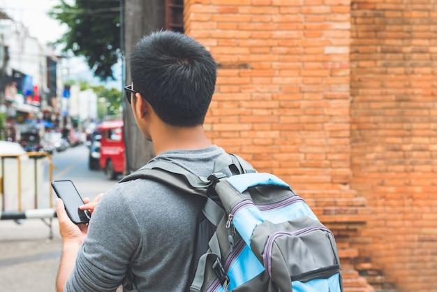 Viaggiatore con zaino e sacco a pelo turistico maschio asiatico che per mezzo dello smartphone che searcing per la posizione mentre viaggiando al portone di tha phae, chiang mai thailand